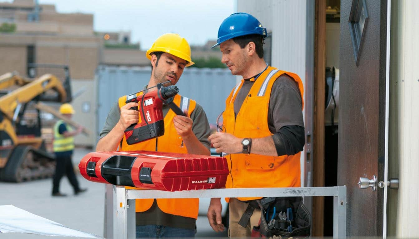two men wearing hard hats on a construction site looking at a te 6-a cordless rotary hammer drill