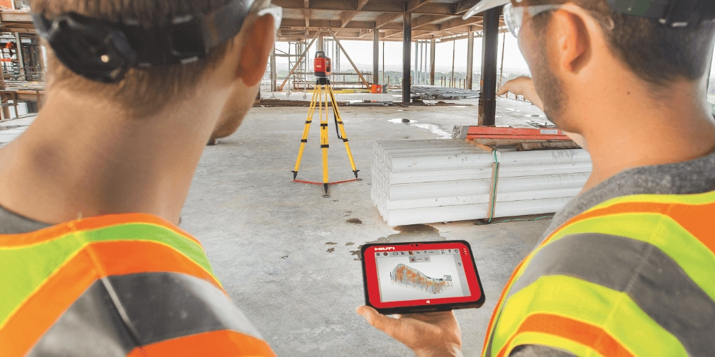 Two construction workers using robotic layout tools to position building elements on the jobsite